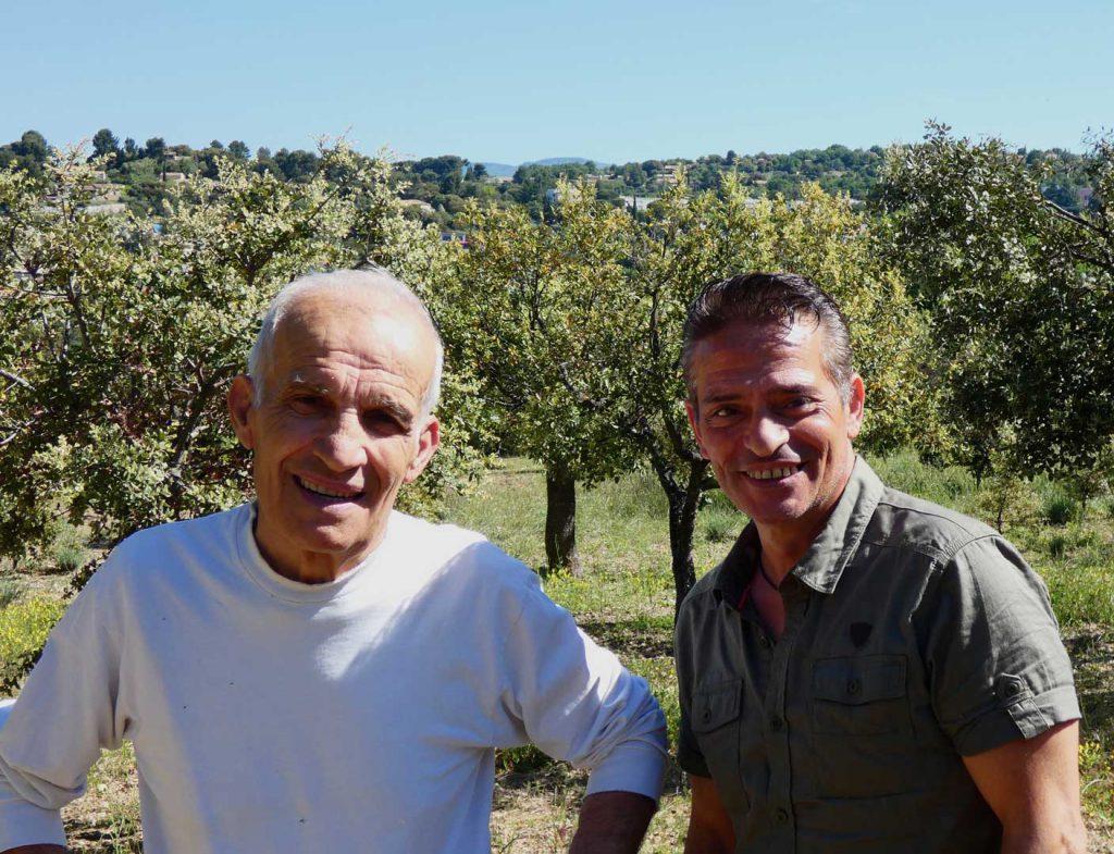 Salvatore et Eric Pinna, le père et le fils, à côté de leur jardin potager et devant des oliviers à Apt