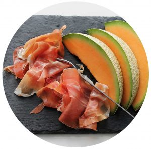 assiette de charcuterie italienne avec du melon sur une ardoise